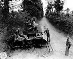 American aviators in Normandy inspecting their work, in this case a knocked out Pz V (Panther). German armour was almost completely prevented from moving in daylight by specialised rocket firing allied ground attack fighters; generally P47 Thunderbolts or Hawker Typhoons.
