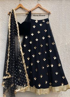 Stylish Black Velvet blouse with gathered net teamed with a Black and Gold skirt with Sequins flowers and a shimmering gold border. Accompanied by a lovely scallop dupatta with gold buttis liberally scattered. Lengha Blouse Designs, Choli Designs, Indian Bridal Outfits, Indian Designer Outfits, Black And Gold Lehenga, Black And Gold Outfit, Indian Gowns Dresses, Teen Dresses, Midi Dresses