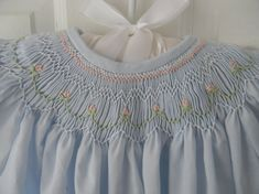 Smocked girls dress - sweet. This is a hand made powder blue Imperial Batiste cotton blend dress with smocked geometric design and flowers all around the top of the dress. Elastic around the sleeve for easy fit and finished with cotton lace edging. The back is finished with 2 mother of pearl buttons and hand made loop closures.  Smocking design looks a lot like Pat Garrettson's > Chloe, that is on this board.