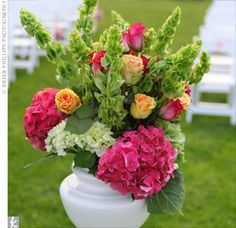 Urns filled with hydrangeas, bells of Ireland, and roses marked the front of the aisle and matched the colors of the wedding bouquets.
