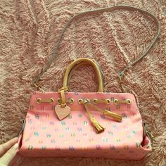 Dooney & Bourke tassel tote Dooney & Bourke tassel tote. Comes with long strap for shoulder or cross body. Pink. Very small makeup stain on interior. Used only twice. Very nice  bag! Dooney & Bourke Bags