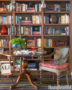 An antique pedestal table and inlaid chair add an Anglo-Indian flavor to an alcove library.