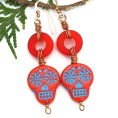 Full of spine tingling, funky fun, these Day of the Dead sugar skull earrings are well named! The SPINE TINGLING handmade earrings feature blazing red Czech glass skull beads. The skulls are highlighted with a turquoise Picasso finish which settled into the recesses of the design, bringing out the awesome detail of the flower eyes, the nose and mouth. #indiemade