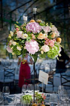 Tall centerpiece in a classical wedding tables with chandeliers in a glass tent. Por A-TIPICA Mesas clásicas con lámparas de araña en una carpa de Cristal. By A-TIPICA