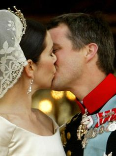Crown prince Frederik and Crown princess Mary of Denmark sealed with a kiss in front of thousands of well wishers standing on the balcony of Amalienborg castle 14 May 2004, after their wedding ceremony at Copenhagen cathedral.