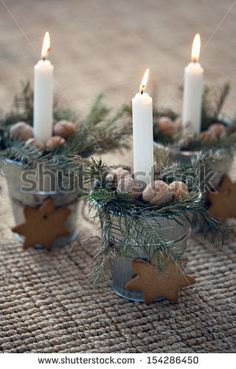 christmas decoration: Burning candle in metal flower pot with cookies with fir branches on beige background
