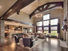 this hearthroom/great room/living room features an open floor plan with a stone fireplace, cedar beams, hardwood floors, great light from the windows, and an amazing light fixture Metal Building Homes, Building A House, Mountain Home Interiors, Montana Homes, Barn House Plans, House Goals, Log Homes, Home Builders, My Dream Home