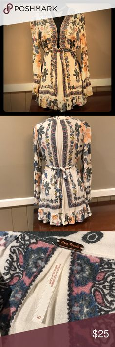 Free people floral Tunic size 10 This top is beautiful! Long sleeved Free People tunic with tie waist and plunging neckline. Floral blues, lavender and peach. Ruffled hem hits mid-hip. Like new condition Free People Tops Tunics
