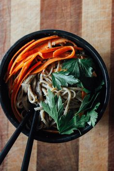 Spicy Peanut Soba Noodles with Veggies *Soba noodles *Peanut butter *Maple syrup *Seasoned rice vinegar *Tamari *Cilantro *Garlic clove *Sesame oil *Ginger root *Cayenne *Nondairy milk or water *Carrots *Hemp or sesame seeds (optional) *Cilantro *Crushed peanuts