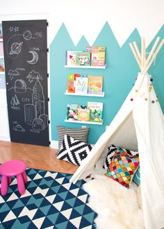 What kid wouldn't love his or her own teepee! Striking and bright colors create a lively environment for this fort-among-forts. Benches double as tables and pillows also work as seats. Kids have easy access to books on a nearby shelf, keeping them organized and not underfoot. A door covered with erasable chalkboard paint provides space for drawing over and over again.