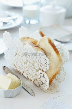 Crocheted doily moulded into original toast rack using fabric stiffener and starch on breakfast table