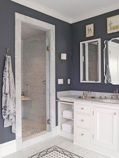 Even the smallest bathroom can accommodate bounteous style. Though diminutive in dimension, this walk-in shower makes an impact thanks to its marble door frame and tiled interior, which are highlighted by charcoal walls. Bathroom floor tiles repeat inside the shower to visually link the two areas.