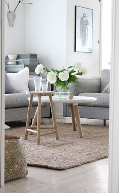 White walls, grey sofa, jute rug, and table