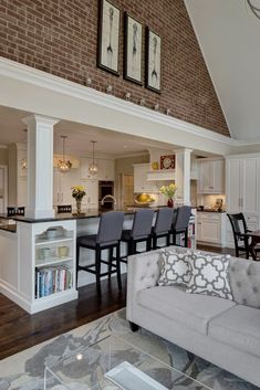 Unbelievable The kitchen expands into the open family room space, emerging beneath an immense vaulted ceiling with a red brick upper dividing wall. Rich dark hardwood flooring contrasts with light gr ..