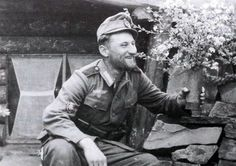 Outside a quarter and a smiling Gebirgstruppen shows his comrades some flowers that he has carefully put inside a 7.5cm artillery shell, probably trying to make his shelter more homely. He wears the typical uniform associated to that of a Gebirgsjager - pin by Paolo Marzioli