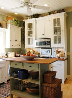 INSPIRATION: The main cabinets are finished in brushed linen white and the island in brushed moss green. The hardware are blackened Shaker wooden knobs.