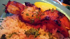 Cajun Maple Bacon Wrapped Shrimp.  8 tail-on shrimp wrapped with thick sliced bacon, charbroiled then glazed with a cajun maple glaze served on a bed of dirty rice