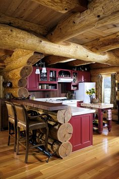 These kitchen cabinets were painted red to complement the tones of the cabin's western red cedar logs. - Cabin Life Magazine