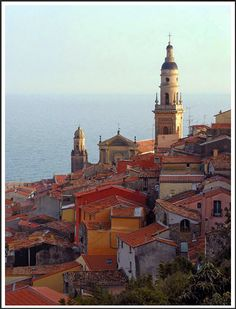 Old Town Menton, French Riviera. This colorful ancient fishing village is nestled against a hillside near the French border with Italy. Old town was in shadow, except for the beautiful St. Michael's basilica towers which glowed in the last rays of the late afternoon sunlight