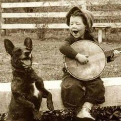A young boy playing the banjo with his dog, circa 1920.