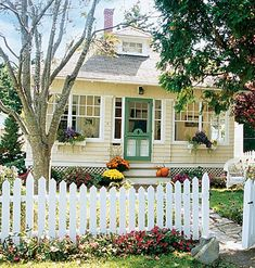 Yellow house with picket fence, green door, window boxes, via my home ideas.com