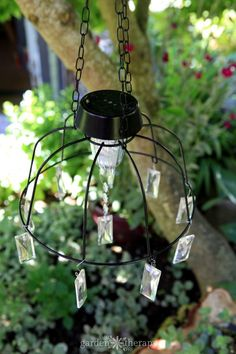 This DIY. This DIY solar light chandelier is an easy project that adds a whimsical touch to the garden. Make this project with a few common materials and some imagination. Solar Light Chandelier, Outdoor Chandelier, Diy Chandelier, Outdoor Lighting, Chandeliers, Fence Lighting, Solar Pathway Lights, Solar Lights, Diy Solar