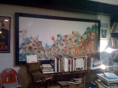 This painting has amazing colors and provides an elegant backdrop to the mess of books crowded around it.