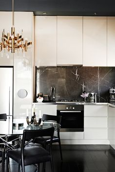 Chic kitchen with cream lacquer cabinets paired with stainless steel countertops and black marble backsplash. Kitchen hood is hidden behind lacquer paneling over small 4-burner gas cooktop with integrated oven. eat-in kitchen features brass art deco chandelier over round glass-top dining table surrounded by glossy black dining chairs with black leather cushions over ebony wood floors.