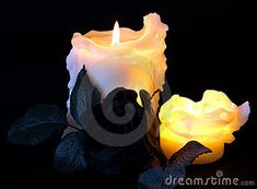 Two lit drippy wax candles with a black rose, against a dark background