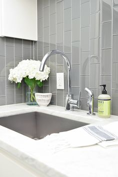 Beautiful laundry room ideas danze kitchen faucet stainless laundry room sink gray subway tile installed vertically white shaker cabinets large stainless bar pulls -7