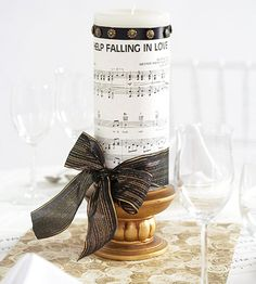 Sheet Music Centerpiece  Bring love songs to a wedding reception by way of centerpieces. Cut sheet music to wrap around a candle, and hold it in place with ribbon and decorative upholstery tacks. For a buffet-style reception, play the songs on the sheet music to signal the guests it's their turn to go through the line