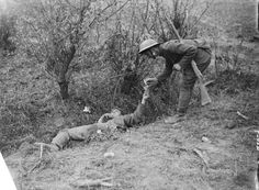 A British soldier gives a cigarette to a severely wounded German in a ditch after the Battle of Pilchem Ridge/31 July 1917