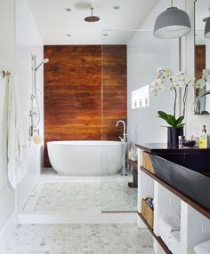 "The Renovation of a Century-Old Denver Bungalow. ""The wood behind the master bathtub and show is reclaimed from the home's original floor joists,"" Lowe says, as well as the vanity shelves. And the vanity bricks are from the original exterior."