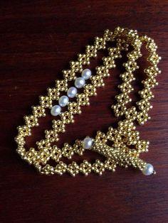 J'ai créé ce bracelet manchette délicate perle et or en tissant une double chaîne de perles de verre or petit dans un modèle de diamant accentués avec des perles d'eau douce blanches de 4-5mm et fermé par un fermoir toggle perlés à la main également agrémenté de perles blanches. Il est simplement élégant design minimaliste, un classique moderne!  Ce bracelet en or est parfait pour une mariée ou pour toute autre occasion spéciale. Il est également assez souple pour être porté comme un…