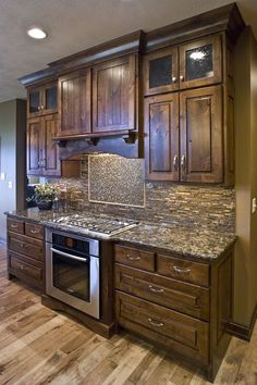 Like the tone of the Rustic Knotty Alder Kitchen Cabinets, would prefer Shaker design. Like the style of glass in the cabinet doors, the covered hood, and the over all craftsman details including the ceiling molding. . Nice countertops.