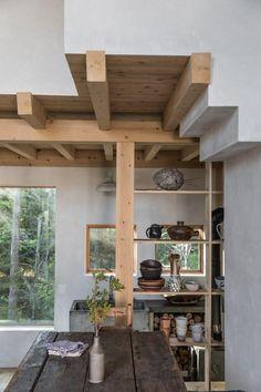 Open cedar shelves display earth-toned ceramics.
