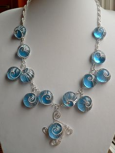 """Blue glass marble and wire woven """"snails"""" jewelry. The link has a tutorial you can buy for 10 dollars, and more pics. I like the colors and ethereal effect, but I'm not crazy about the snail motif."""