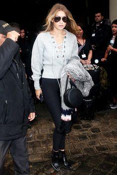 Gigi Hadid wears a lace-up sweatshirt, leggings, black boots, and aviator sunglasses