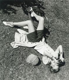 Outfit: appears to be blouse & skirt set, skirt unbuttoned for shorts & biking. Note bangles & ghillie style shoes ALady. Snapping Photos, 1949
