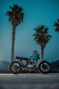 A sleek ocean-blue Kawasaki W650, stripped to the essentials and ready for a blast down the beach in Greece. Does it get any better?