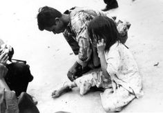 A Vietnamese Marine aids a child wounded during the Tet Offensive, 1968.