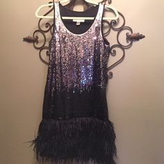 Michael Kors Sequin Feather Cocktail/Prom Dress All eyes on you. Silver sequins morph through midnight tones drawing the eye down the figure-hugging length of a stretchy sheath. Ostrich feathers take over at the hips to finish the flirty, abbreviated style.  Slips on over head, has side zipper. Fully lined. 100% polyester with genuine ostrich feathers. Dry clean. By MICHAEL Michael Kors; imported. MICHAEL Michael Kors Dresses Prom