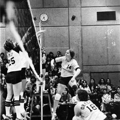 Black and white photo of University of Oregon volleyball player Kathy Young (#18) just after setting the ball for teammate Shawna Baxter (#14) during a game played against Portland State at the Gerlinger Annex in 1975. ©University of Oregon Libraries - Special Collections and University Archives