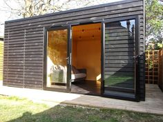 Gym in the garden with storage shed and black stained cladding