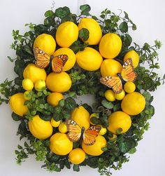 """This beautiful Spring, Summer Lemon flower door wreath sets on a nature grapevine wreath base.  The wreath is embellished with lots of greenery. The wreath is accented with 16 large (4.5"""") yellow Lemons, nine small Lemons and three medium Lemons. I finish the wreath with three lovely yellow/black Butterflies.  The wreath measures from tip to tip at 22"""" (L) x 22"""" (W) x 7""""(D)."""