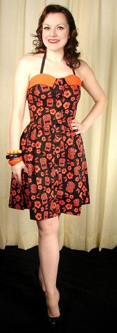 Orange Tiki Halter Dress - This sun dress is so different from any dresses out there. It is black with orange trim along the bustline and orange tikis and hibiscus flowers throughout. It is fitted on top with halter ties and almost of full back of shirred elastic to fit perfect. The skirt is gathered all the way around the waist to create fullness and the dress buttons all the way down the front. $52