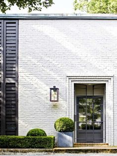 white painted brick facade; contemporary brick portal frame effect entrance; wall lantern; black full-height shutters