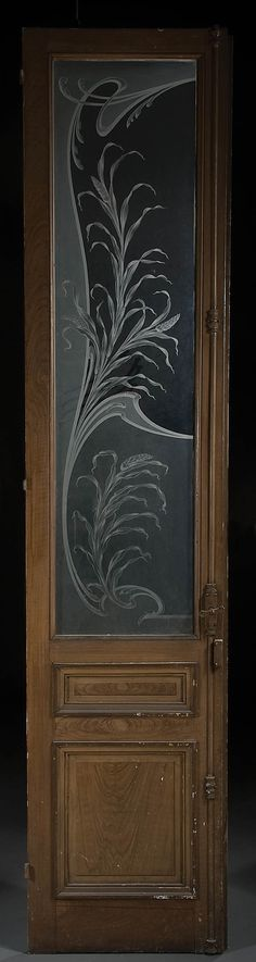 FRENCH ART NOUVEAU CAMEO GLASS AND WALNUT ENTRY DOOR late 19th century, acid etched in three layer relief in gray transparent glass with stylized foliage design above a recessed door panel.