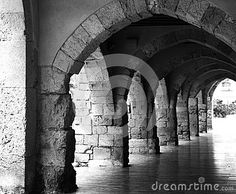 A black and white image of an outdoor hallway made of stone arches in the town of Tarragona Spain.