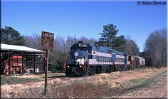 The same train as pictured above is now at Raeford as it nears a rural grade crossing protected by a rusty and aged sign.